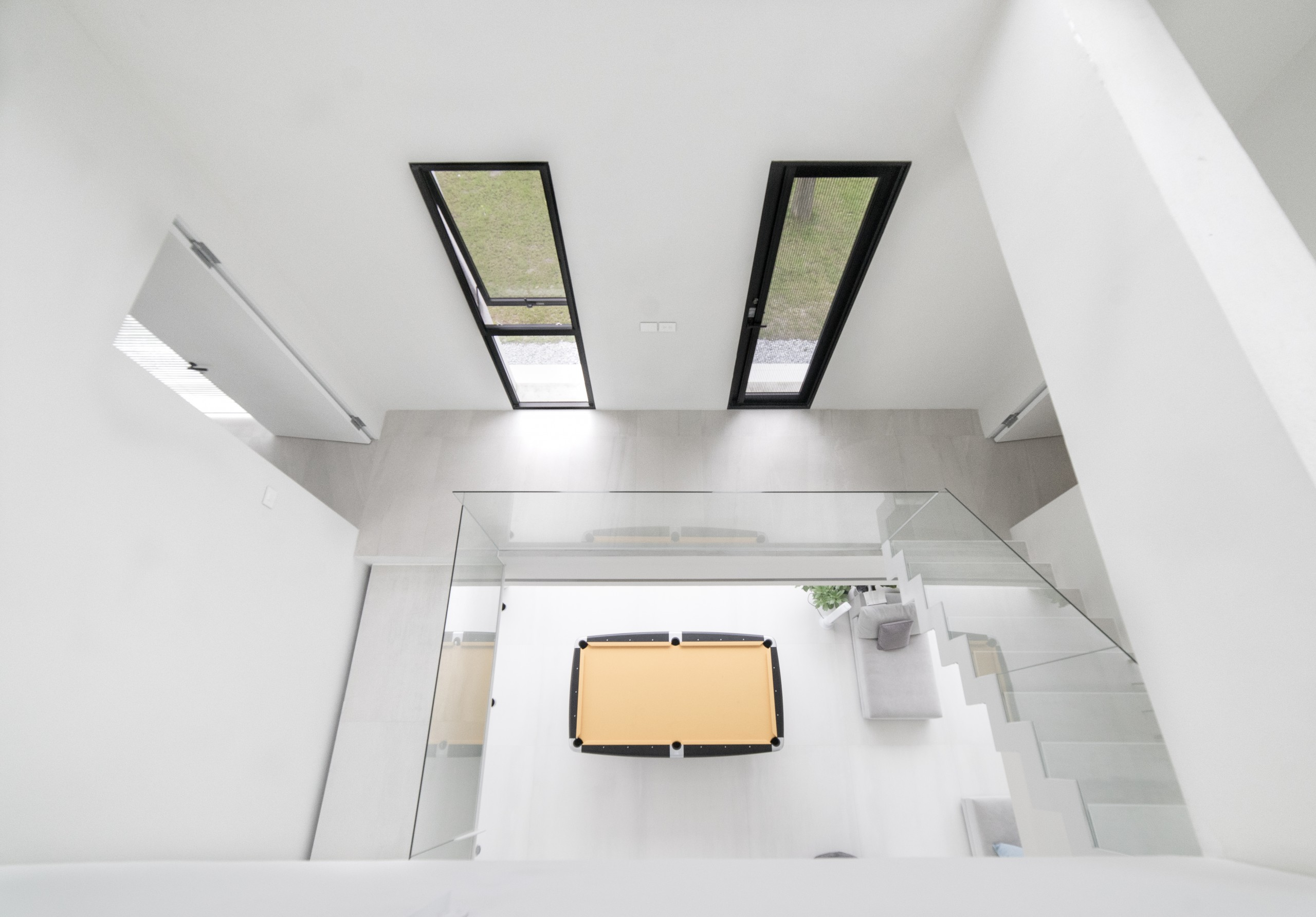 ©三層挑高的樓梯搭配一樓中央的大撞球桌,為空間添增愉悅的氛圍